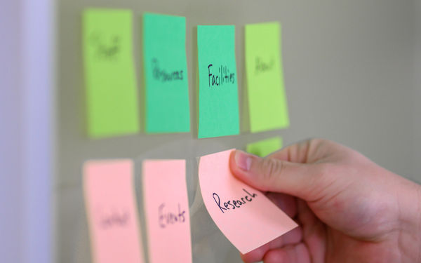 Two rows of four sticky notes labeled with sections of a site such as events, research, and facilities.